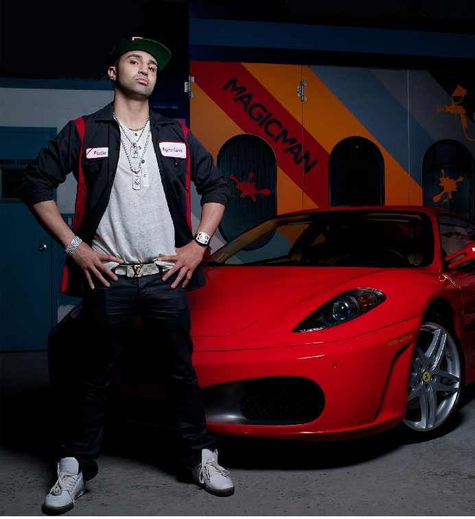 Paulie Malignaggi standing in front of his red Ferrari F430 while wearing a grey shirt, black jacket and black pant