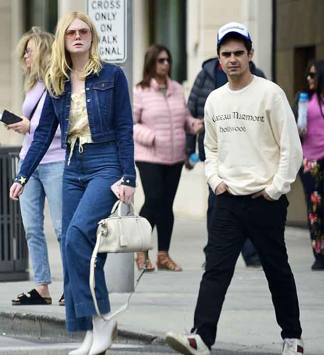Elle Fanning and Max Minghella walking down in street.