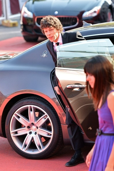 Jesse Eisenberg getting out of his black Maserati in his Tuxedo