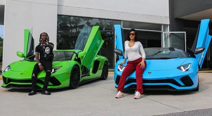 Cardi B standing in front of her blue Lamborghini while Offset in front of his green Lamborghini