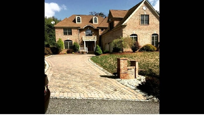 Juelz Sanata brown colored house made of brick with a long entry pathway
