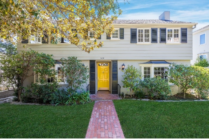 Tony Hale's traditional two storey house with a yellow door and a green lawn at front