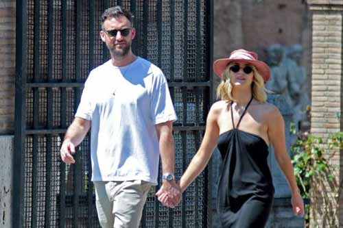 A picture of Jennifer Lawrence and Cooke Maroney walking down street holding one another hand.