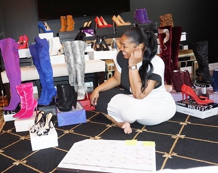 A picture of Rashidah Ali sitting along with the shoes at her shop.