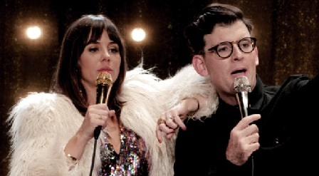 A picture of Moshe Kasher and Natasha Lehhero holding the mic in their show The Honeymoon Stand Up Special.