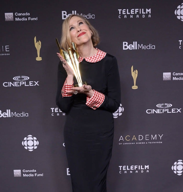 Catherine O'Hara wearing black dress while looking up and smiling holding her golden Canadian Screen Award
