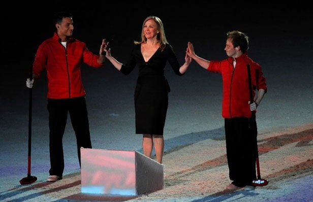 Catherine O'Hara in black dress while joining hands with two boys wearing same clothes, red jacket and black pant while performing at Winter Olympics