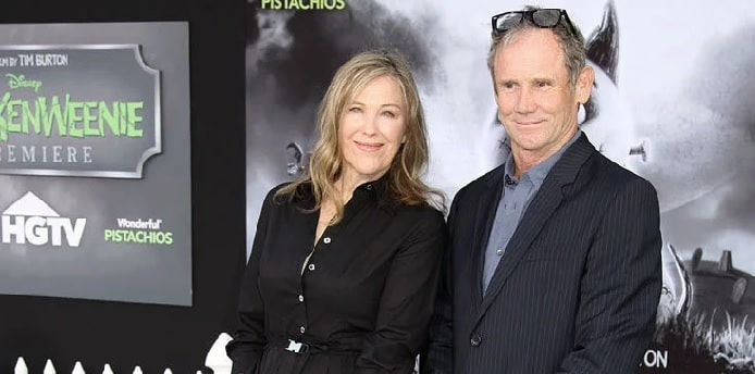 Catherine O'Hara in black dress with her husband smiling who is in blue shirt black coat