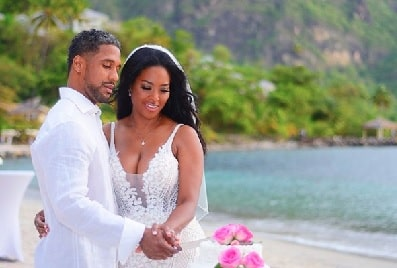 Marc Daly and Kenya Moore holding their hands while posing on their wedding day.