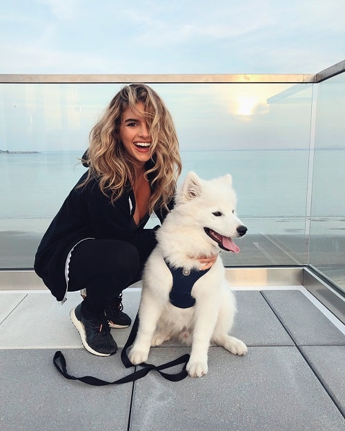 A picture of Alana Paolucci posing with a white dog.