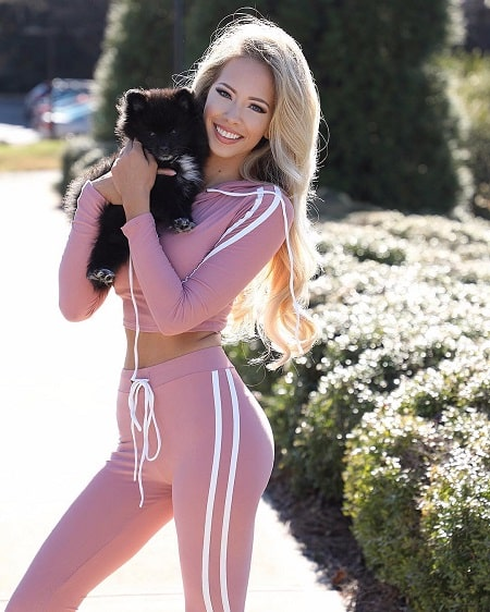 A picture of Amanda Taylor modeling with her pet dog, Koda.