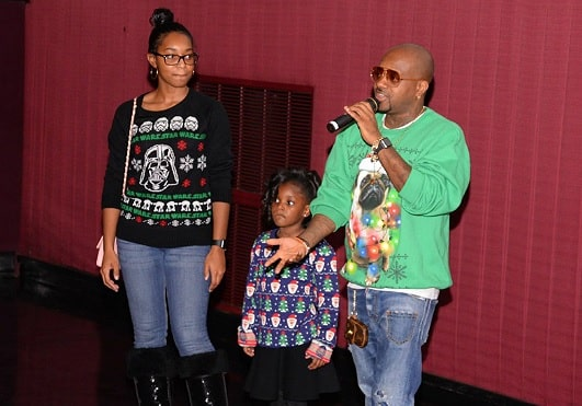 Jermaine Dupri in his green sweater while holding the mic with his two daughters Shaniah Mauldin on the left and Jalynn Mauldin in between