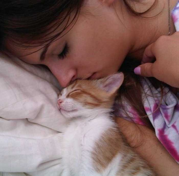 A picture of Lis Giolito sleeping with her cat.