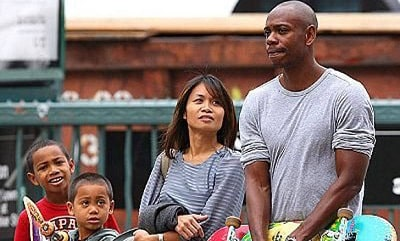 A picture of Dave Chappelle in public with his sons and wife.