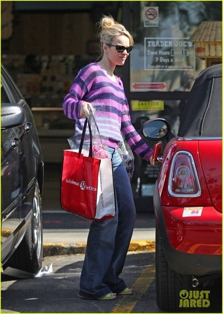 A picture of Rachel McAdams with her red mini Cooper car.