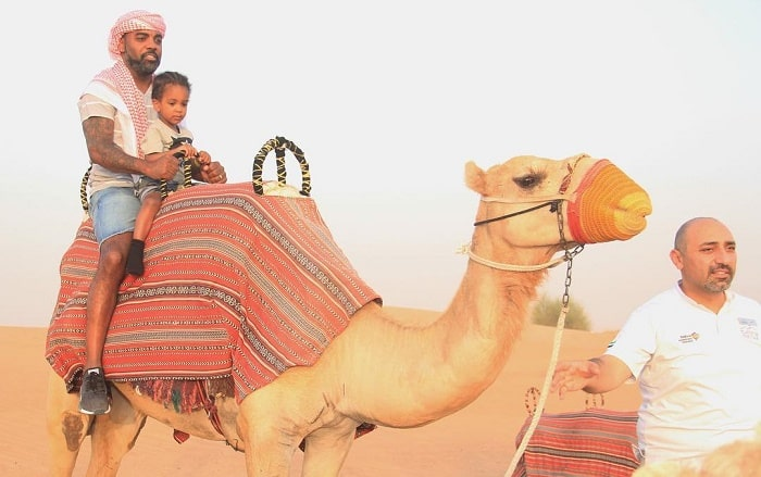Ace wells riding in camel with his dad in Dubai.