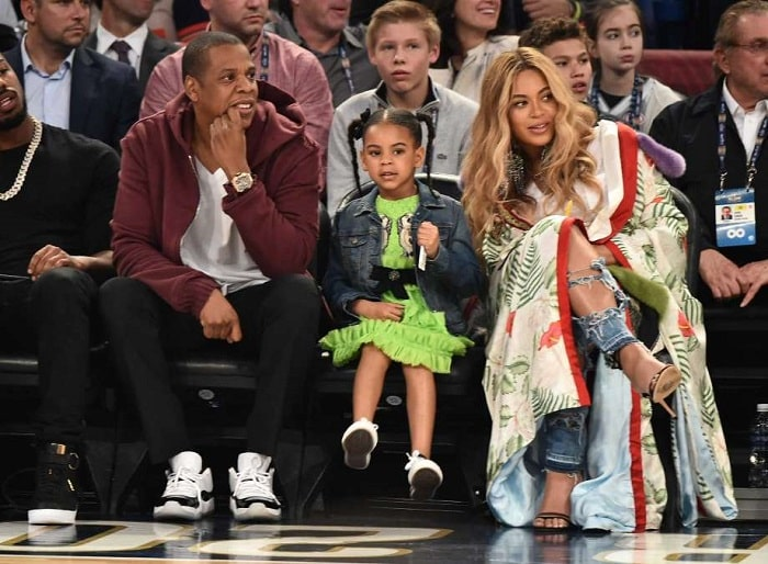 Blue Ivy Carter sitting with her parents Jay Z and Beyonce .