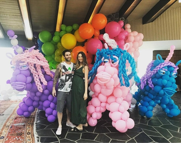 A picture of Adam and pregnant Behati in their first daughter's birthday.