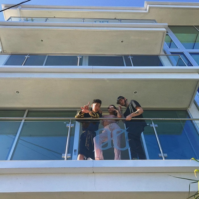 RiceGum posing out of his balcony with his friends.