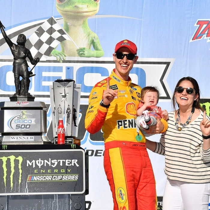A picture of Logano celebrating his victory with his wife and son.