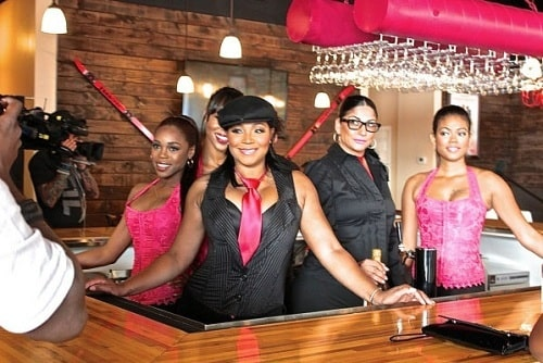 "A picture of Trina Braxton and her staffs in her restaurant ""Bar Chix""."