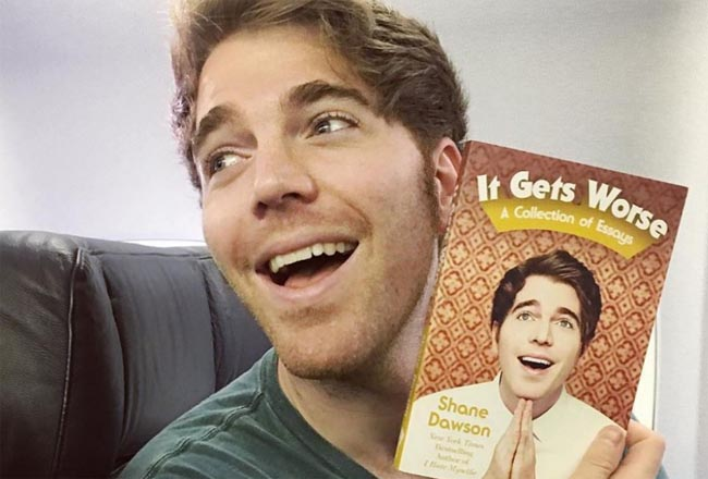 "Shane taking a picture with his book ""It Gets Worse""."