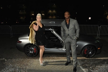 A picture of Rebecca King - Crews and her husband, Terry Crews with her silver Mercedes-Benz.
