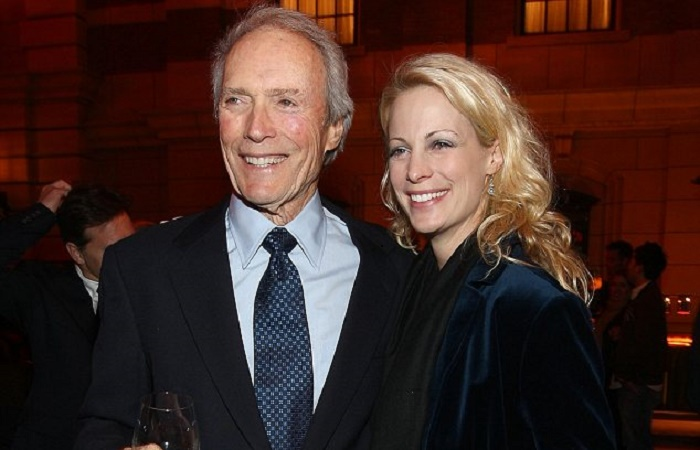 Jacelyn Reeves and Clint Eastwood poses for a picture.