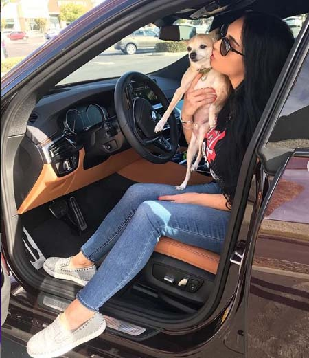 Paris Roxxane take a picture with her dog in a car.