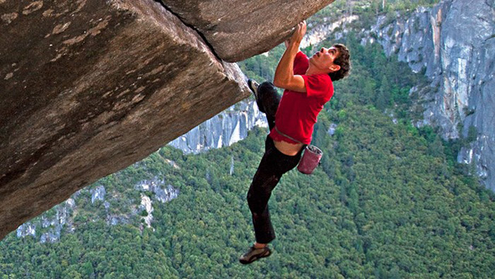 Alex Honnold climbing a rock without a rope.