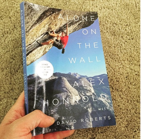 Alex Honnold taking a picture of his book for promotion post.