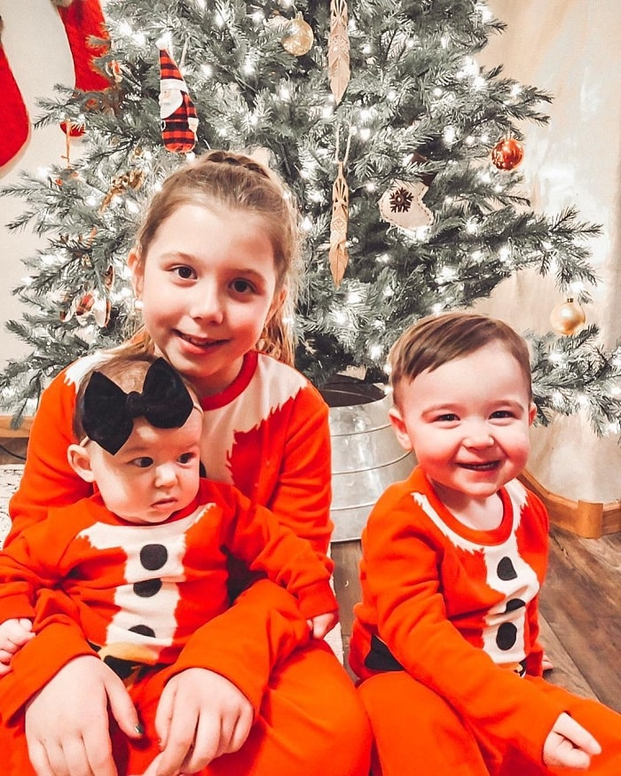 The 3 siblings celebrating Christmas with matching onesies.