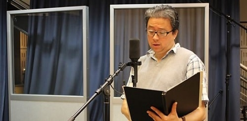 A picture of Paul Courtenay Hyu reading script.
