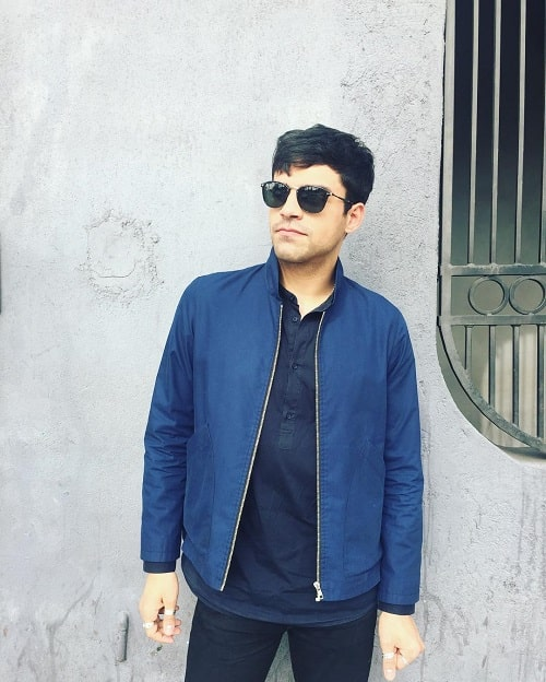 A picture of Sean Teale wearing blue jacket and sunglasses.