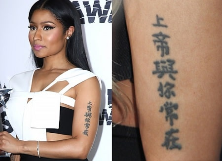 A picture of The Chinese Writing tattoo of Nicki Minaj on her left upper arm.