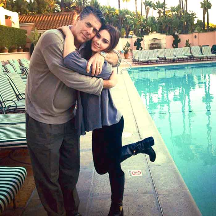 McKayala Maroney and Mike Maroney poses for a picture hugging one another.
