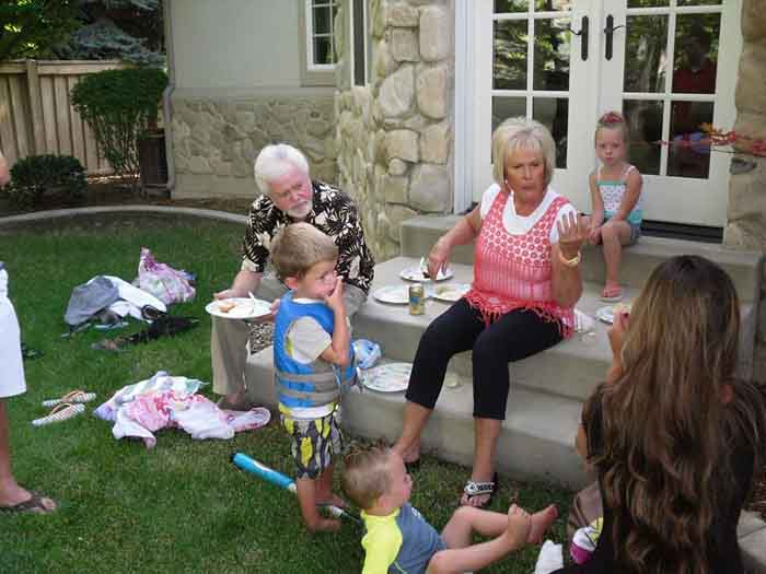Mary Carlson and her husband Merrill Osmond playing with their grand children.