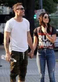 Brian and his wife Megan Fox holding hands.