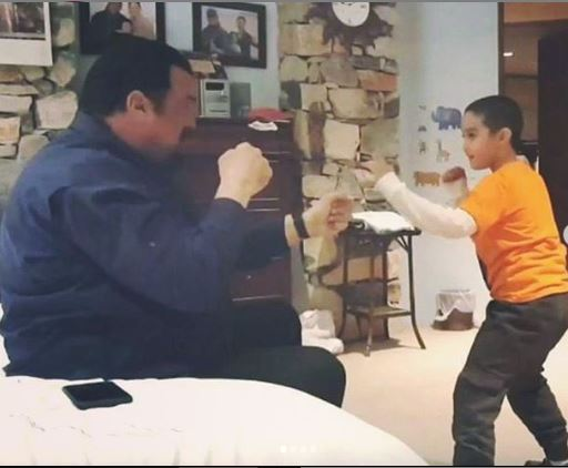 A picture of Kunzang Seagal playing play-fight with his dad Steven Seagal.