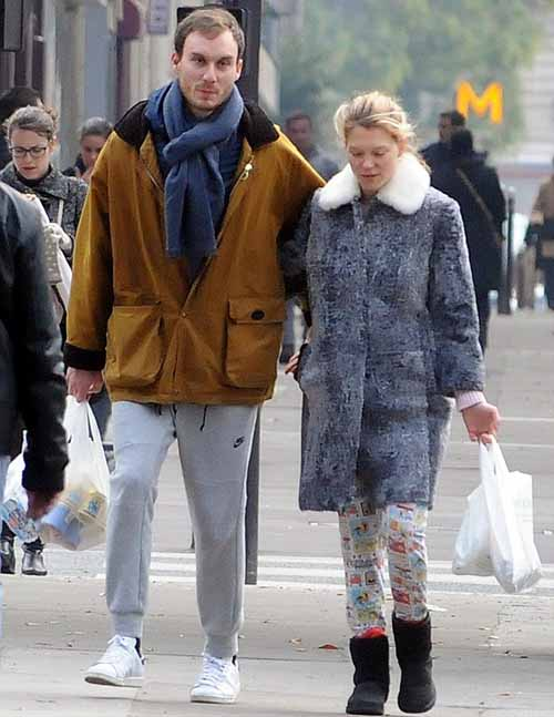 Lea Seydoux and Andre Meyer walking on down street.