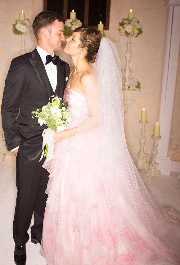 Jessica Biel and Justine Timberlake facing each and smiling while Jessica on her pinkish-white gown catching a bouquet and Justine in a Tuxedo.