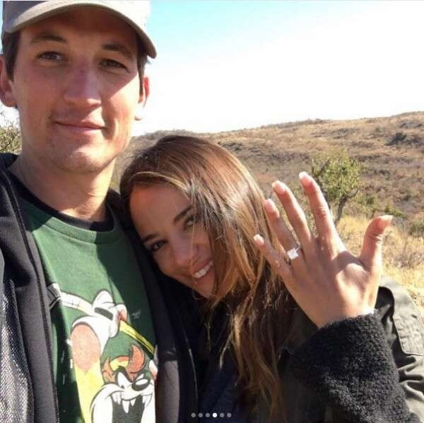 Keleigh Sperry showing her hand while wearing engagement ring while Miles Teller hugging her