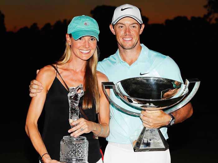Erica Stoll and her husband Rory Mcllroy poses with a trophies.