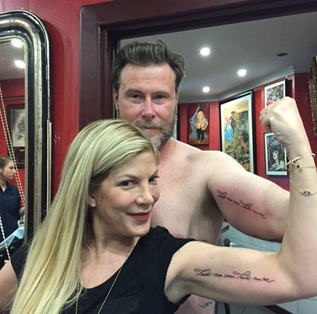 A picture of Tori Spelling with her husband flaunting their matching tattoos.