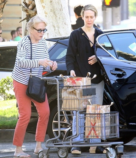 A picture of Holland Taylor and her partner Sarah Paulson putting their groceries in their black Mercedes.