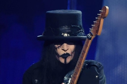 A picture of Mick Mars holding his guitar.