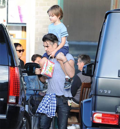 A photo of Colin carrying son in his shoulder's.