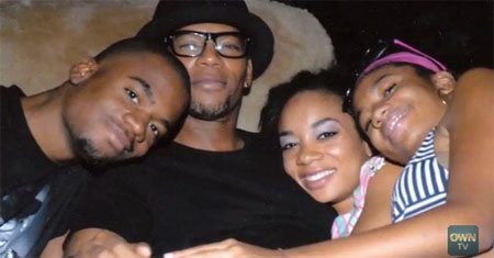 D. L. Hughley posing for a photo with his children.