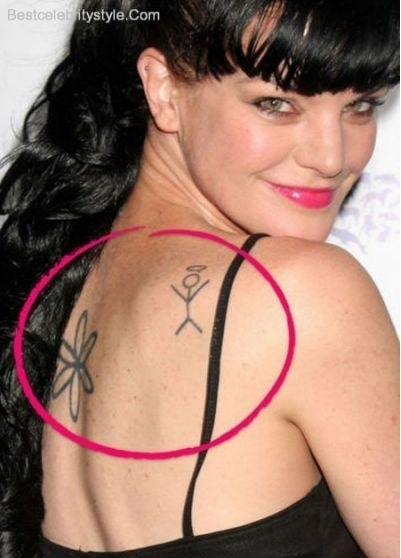 Pauley Perrette showing her daisy flower and stick figure tattoo.